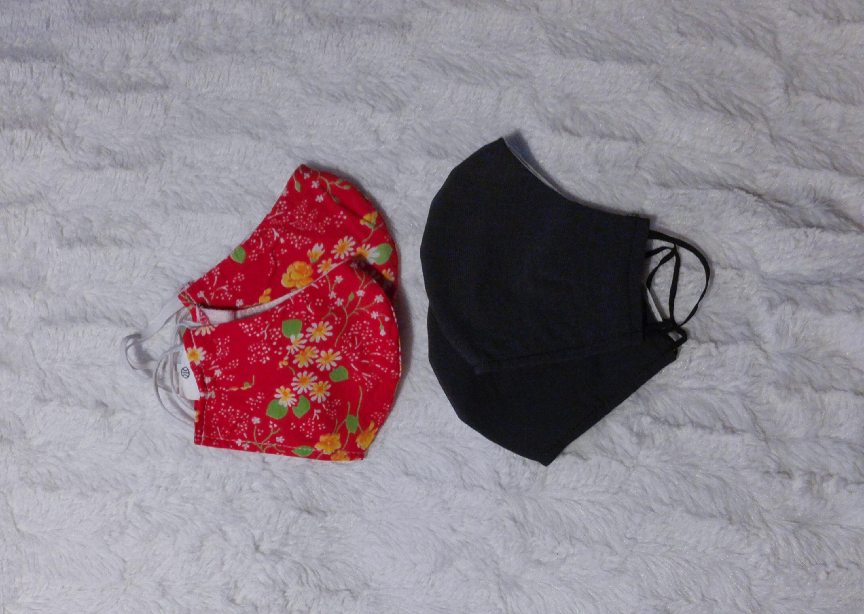 Neljä kangasmaskia valkoisella taustalla. Kaksi pienempää punaista maskia, jossa on kukka kuvio ja kaksi isoa mustaa maskia.