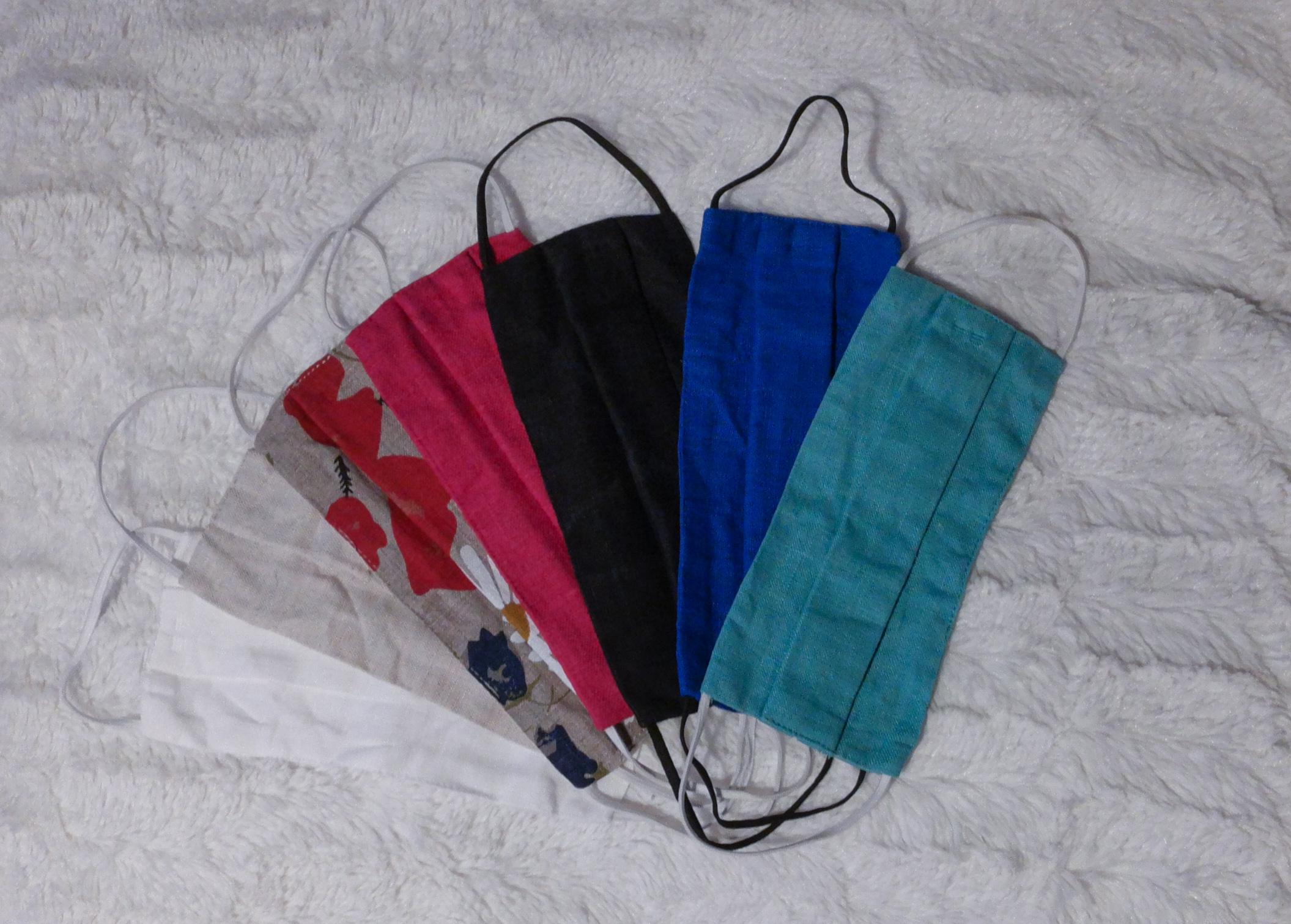 Seitsemän kangas kasvomaskia valkoisella taustalla. Yksi valkoinen, yksi beessi, yksi beessi jossa on punainen kukkakuvio, yksi magenta, yksi musta, yksi tummansininen ja yksi turkoosi.